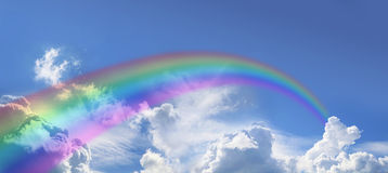 Huge arcing rainbow on wide blue sky Stock Image