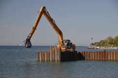 Huge backhoe drives pilings into the water Stock Photos