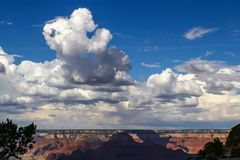 Huge billowing clouds in a blue sky above the Grand Canyon with dramatic shadows stock image