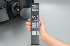 Huge black home cinema projector, hand presenting the remote.  Royalty Free Stock Photography