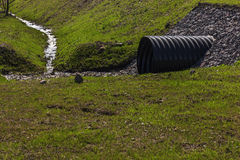 Huge black plastic sewer and small stream Royalty Free Stock Photos