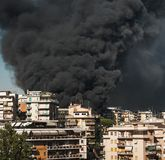 Huge black smoke from a fire in a big city. Panoramic view from a distant distance. A real event. Italy Rome Royalty Free Stock Photo