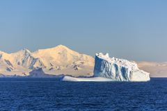 Huge blue iceberg drifting across the sea in the middle of nowhere, Antarctica. Huge blue iceberg drifting across the sea at Lemaire Channel, Antarctica stock photography
