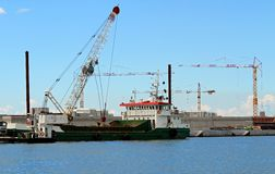 Huge boat for transporting goods in the huge construction site Stock Images