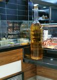 Huge bottle of olive oil. Big glass bottle of yellow olive oil stand on counter in cafe Stock Photography