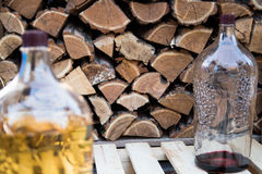 Huge bottles of homemade wine. Stand on the background of a wooden wall Stock Photography