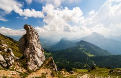 Huge boulder and green hills in the mountains. Huge boulder, bright clous and green hills in the Chartreuse mountains in Alps near Grenoble, France Stock Photography