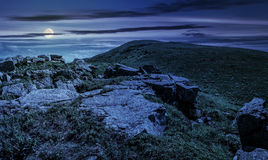 Huge boulders on the edge of hillside at midnight. Fine weather in summer mountain landscape at night in full moon light stock images