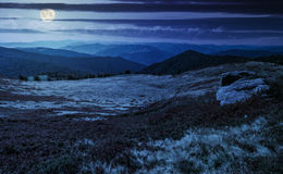 Huge boulders on the edge of hillside at night. In full moon light. fine weather in summer mountain landscape royalty free stock photos