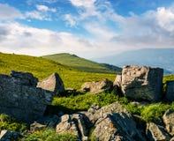 Huge boulders on a grassy hillside at sunrise Stock Photos