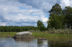 Huge boulders in northern Karelian lake. The beautiful picture of Karelian forest at the edge of a lake, and some huge boulder in this lake stock images