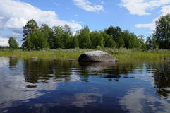 Huge boulders in northern Karelian lake. The beautiful picture of Karelian forest at the edge of a lake, and some huge boulder in this lake royalty free stock image