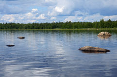 Huge boulders in northern Karelian lake. The beautiful picture of Karelian forest at the edge of a lake, and some huge boulder in this lake royalty free stock photography