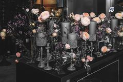 A huge bouquet of beautiful English roses is decorated in the interior with beautiful gray candlesticks and candles of various. Sizes royalty free stock photo