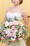 Huge bouquet in young bride`s hands stock photography