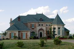Huge Brick House on Lake. Huge brick modern French provincial style house with ornate fountain and beautiful landscaping royalty free stock images