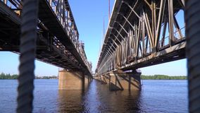View from under the bridge over the river. A huge bridge across the river on a cloudless day stock footage