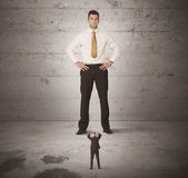 Huge business guy looking at small coworker Royalty Free Stock Images