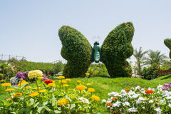 Huge butterfly sculpture made from plants on the grass field surrounded by flowers Stock Photos
