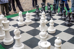 A huge chessboard on which the battle in the tournament children playing with white and black pieces in the open air on the street Royalty Free Stock Photo