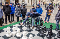 A huge chessboard on which the battle in the tournament children playing with white and black pieces in the open air on the street Royalty Free Stock Images