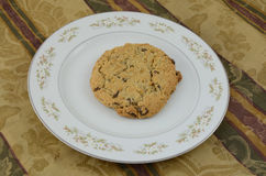 Huge chocolate chip cookie on plate on tablecloth Royalty Free Stock Photos