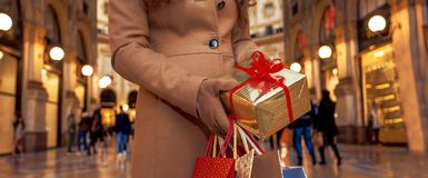Closeup on Christmas gift and shopping bags in hands of woman Stock Image