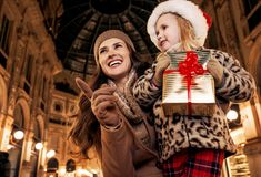 Mother and daughter with Christmas gift pointing on something Royalty Free Stock Photos