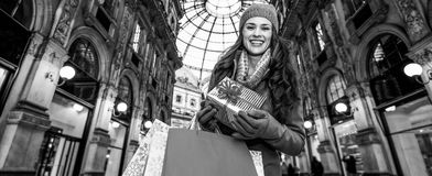 Happy woman with Christmas gift and shopping bags in Milan. On a huge Christmas sales in Italian fashion capital. Portrait of happy young tourist woman with royalty free stock images
