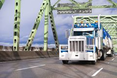Huge classic blue big rig semi truck with grille guard bumper an. D covered cargo on flat bed trailer going through trusses bridge across Columbia river with royalty free stock photo