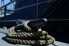 Huge cleat and heavy rope. The heavy gauge rope around the iron cleat is securing a submarine to the dock Royalty Free Stock Photos