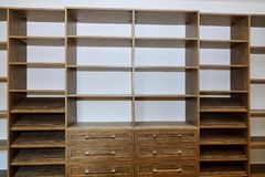 Huge closet with shelves, drawers and shoe racks. With wooden shelves wall installing a shelf royalty free stock photos