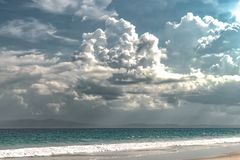 Landscape of Strange Weather Phenomenon due to Climate Change, comprising dramatic dark clouds alongside natural beach in monsoons royalty free stock images