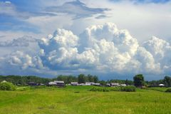 A huge cloud over the small village Stock Image