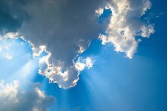 Huge cloud with sun behid them stock image