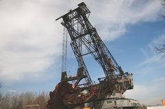 The huge coal mining machine. Captured from a side with sky and trees in background Royalty Free Stock Photos