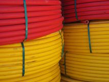 The huge coils of yellow and red cable are stacked one above the other, red on top, yellow from below. Royalty Free Stock Photos