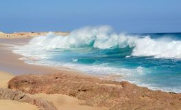 Huge Colorful Wave Breaks on a Beach in Mexico. Huge Surf in Cabo San Lucas Mexico with bright colored water and sand Stock Image