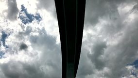 Huge concrete bridge. Used for car traffic over a deep valley. Camera follows pillar up along the underside against dramatic sky stock video footage