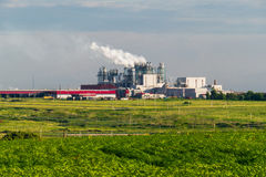 A huge concrete plant with pipes among the fields.  Royalty Free Stock Images