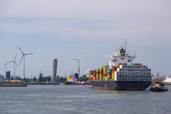 Huge container ship tugged in Antwerp container terminal Stock Photo