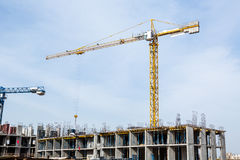 Huge crane and construction plant. Big construction crane and the building against the sky background. Tower Crane in Construction site Royalty Free Stock Images