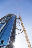 Huge crane rising near construction of a skyscraper Stock Photos