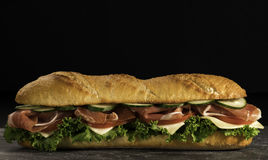 Huge crispy baguette sandwich with meat and vegetables. Close up. Huge fresh crispy baguette sandwich with meat, prosciutto, cheese, lettuce salad and royalty free stock photography