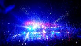Crowd of people being showered in streamers and confetti at a rock concert. Huge crowd of people uner blue lights being showered in confeti and streamers at a Royalty Free Stock Photos