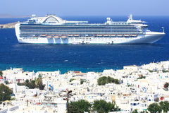 Huge cruise ship at anchor at mykonos island. Very big cruise liner at anchor at sea next to the white washed village in the island of mykonos with its white Stock Image