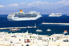 Huge cruise ship at anchor at mykonos island. Very big cruise liner at anchor at sea next to the white washed village in the island of mykonos with its white Royalty Free Stock Image