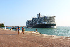 Huge cruise ship passing near shore. A huge cruise ship is passing near the shore in Venice. Some people admire the big ship while walking on the seafront Stock Photography