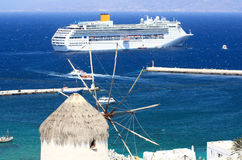 Huge cruise ship and a windmill in mykonos. Traditional mykonian windmill and a very big cruise liner at anchor in the blue sea Royalty Free Stock Images
