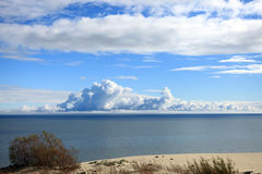 A huge clouds above the sea horizon in a clear wea. Huge cumulus clouds above the Baltic Sea from the Curonian Spit sandy coast on a clear autumn day Royalty Free Stock Photo